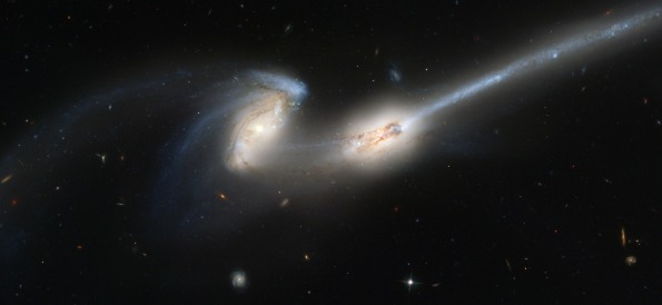 Two galaxies colliding, throwing off tidal tails as they close in.  NGC4686 photo courtesy NASA and the Hubble Space Telescope.