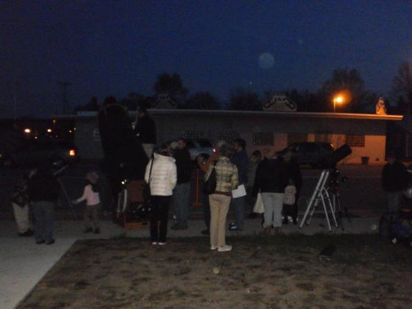 A  crowd gathers to view Saturn and Jupiter.