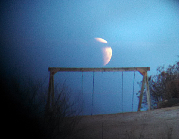 Partially eclipsed Moon setting
